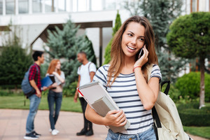 Happy lovely young woman student standing and talking on cell phone outdoors