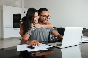 Happy loving couple using laptop and analyzing their finances. Looking at laptop.