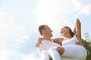 Happy male holding his girlfriend on hands with blue sky above