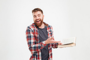 Happy male student standing and holding book isolated on a white background
