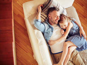 Happy man and his daughter relaxing on sofa