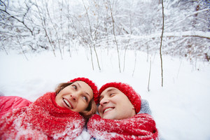Happy man and woman lying in snowdrift in winter park