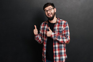 Happy man dressed in shirt in a cage and wearing glasses standing over chalkboard and make thumbs up gesture.