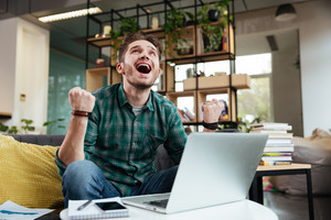 Happy man in green shirt sitting on sofa by the table with laptop and looking up with open mouth in office. Coworking