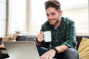 Happy man in green shirt sitting on sofa with cup of tea and looking at laptop. Coworking
