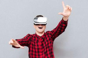 Happy Man in red shirt in virtual reality device showing camera sign with open mouth. Isolated gray background