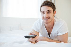 Happy man lying on bed and wathcing TV