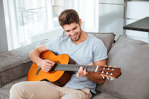 Happy man playing on the guitar while sitting on sofa at home. Looking at guitar.