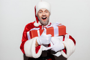 Happy man santa claus holding gift boxes and showing ok sign