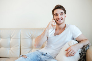 Happy Man talking at phone and sitting on sofa