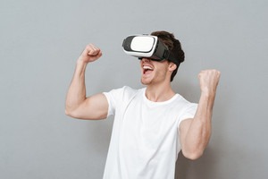 Happy man using virtual reality device with open mouth. Isolated gray background
