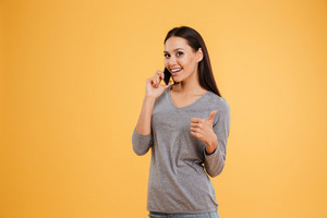 Happy model talking on phone and looking at camera. isolated orange background