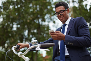 Happy modern businessman using cellphone in park