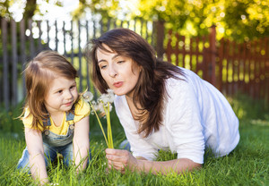 Happy mother and daughter outside in green nature