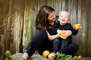 Happy mother and little son sitting by the wooden fence and eating orange