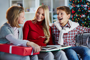 Happy mother and two kids reading and discussing tales on Christmas evening