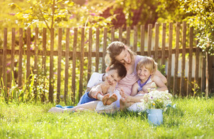 Happy mother with her children spending time together outside in green nature.