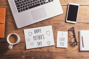 Happy mothers day and I love you sign. Office desk. Studio shot on wooden background.