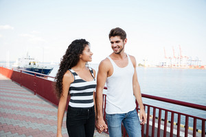 Happy multiethnic young couple in love walking and holding hands in port
