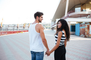 Happy multiethnic young couple standing and holding hands in port