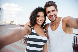 Happy multiethnic young couple standing and taking selfie outdoors