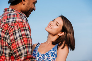 Happy multiethnic young couple standing outdoors over blue sky background
