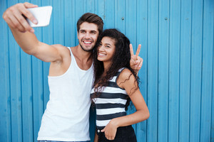 Happy multiethnic young couple taking selfie and showing peace sign over blue background