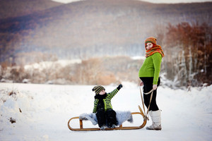 Happy mum with her son riding on sledge having fun outside in the snow.
