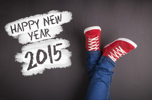 Happy new year 2015. Christmas concept with red sneakers and white chalk text on black floor