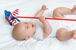 Happy newborn baby girl playing with a pinwheel in her house