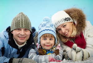 Happy parents and their daughter in winterwear lying in snow