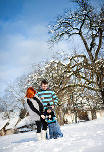 Happy parents with child having fun outside in snow