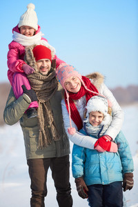 Happy parents with kids in winterwear looking at camera outside
