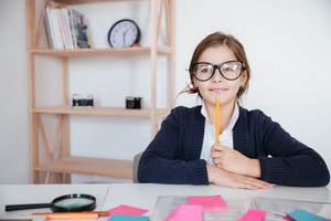 Happy pensive little girl in glasses sitting and thinking at the table