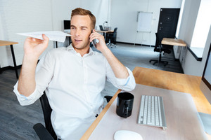 Happy playful young businessman talking on mobile phone and throwing paper plane in office