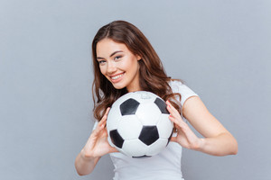 Happy playful young woman smiling and holding football ball