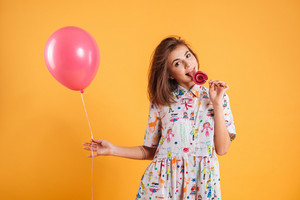 Happy playful young woman with pink balloon eating and licking lollipop over yellow background