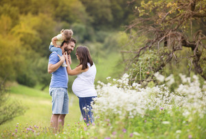 Happy pregnant family having fun in summer nature