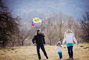 Happy pregnant family having fun with kite in autumn nature