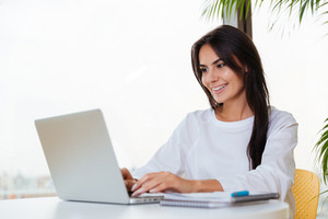 Happy pretty young businesswoman smiling and using laptop in office