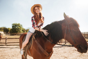Happy pretty young woman cowgirl riding horse on ranch