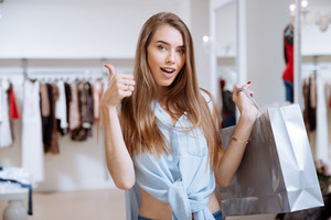 Happy pretty young woman holding shopping bag and showing thumbs up in clothing store