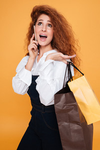 Happy pretty young woman holding shopping bags and talking on cell phone