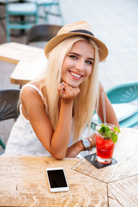 Happy pretty young woman in hat with blank screen mobile phone drinking cocktail in outdoor cafe