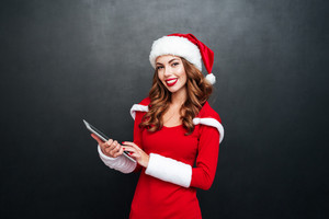 Happy pretty young woman in santa claus costume standing and using tablet isolated on a black background