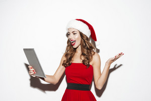 Happy pretty young woman in santa claus costume standing and using tablet