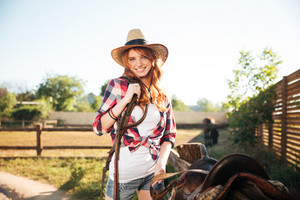 Happy redhead young woman cowgirl preparing saddle for riding horse