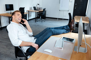 Happy relaxed young businessman sitting with legs on table and talking on cell phone in office