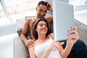 Happy relaxed young couple lying and using tablet on sofa at home