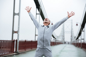 Happy runner in gray sportswear standing on bridge with hands up